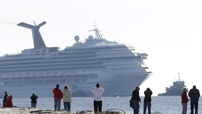 People on Spanish Fort watch as a disabled Carnival Lines cruise ship is towed to harbor off Mobile Bay, Ala., Thursday, Feb. 14, 2013. The ship with more than 4,200 passengers and crew members has been idled for nearly a week in the Gulf of Mexico following an engine room fire. (AP Photo/Gerald Herbert)