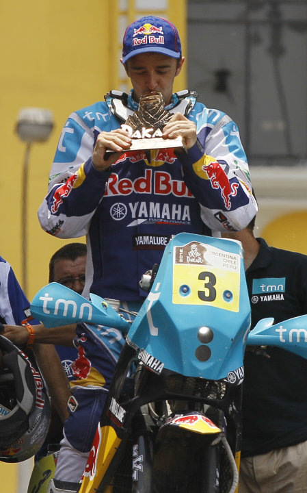 Yamaha biker Helder Rodrigues of Portugal kisses his trophy, celebrating his third place win in the motorbike overall category during the 2012 Argentina-Chile-Peru Dakar Rally podium ceremony in Lima,