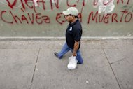 "A man walks past a graffiti reading ""Tell the Truth, Chavez is Dead"" in Caracas on January 8, 2012"