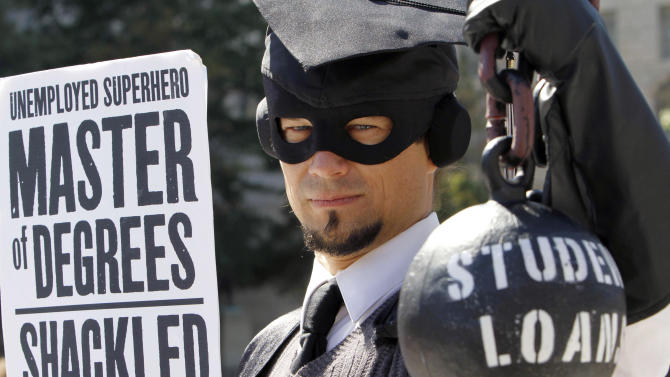"FILE - In this Oct. 6, 2011, file photo, Gan Golan, of Los Angeles, dressed as the ""Master of Degree,"" holds a ball and chain representing his college loan debt, during a protest in Washington. A new report shows two-thirds of the national college class of 2011 finished school with loan debt, and those who borrowed walked off the graduation stage owing on average $26,600. That's up about 5 percent from the class before. (AP Photo/Jacquelyn Martin, File)"