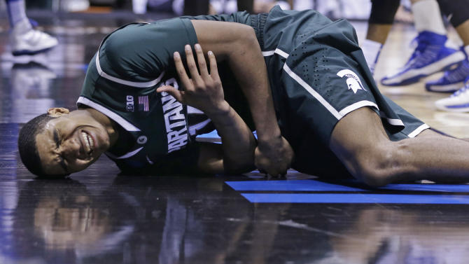 Michigan State guard Gary Harris (14) reacts on the floor as he comes down after getting fouled by Duke guard Seth Curry (30) during the second half of a regional semifinal in the NCAA college basketball tournament, Friday, March 29, 2013, in Indianapolis. Duke won 71-61. (AP Photo/Darron Cummings)