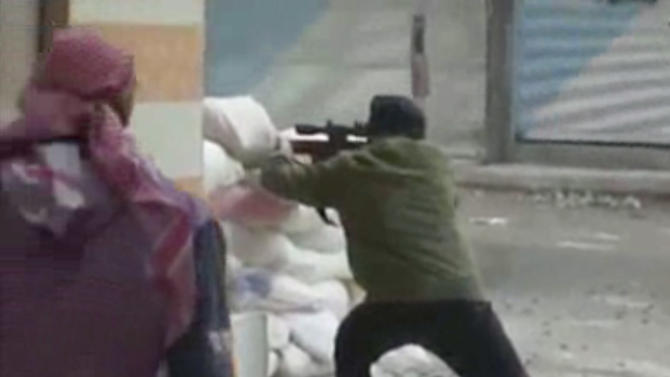This image from amateur video AP obtained from Ugarit News has been authenticated based on its contents and other AP reporting and shows a rebel firing a weapon around a corner at Syrian government forces in Damascus, Syria Friday Dec. 7, 2012.  Fighting around the Syrian capital has intensified in recent days as rebels press a battle they hope will lead to the collapse of  President Bashar Assad's regime after 20 months of conflict. (AP Photo/Ugarit News via AP Video)