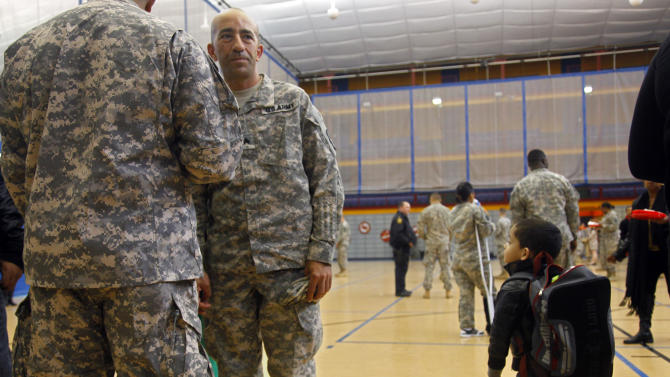 """Sgt. Anthony Regolino, second from left, was among 160 soldiers of the New York Army National Guard's 442nd Military Police Company, deployed in Afghanistan for ten months, who returned to a homecoming ceremony at the the New York Army National Guard facility in the Harlem neighborhood of New York on Friday, April 8, 2011.  Regolino, from Mastic Beach, N.Y., says that he is """"worried about finding a job."""" Adding, """"If the government closes down we get no paychecks."""" (AP Photo/Bebeto Matthews)"""