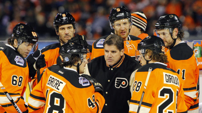 Philadelphia Flyers coach Peter Laviolette, center, huddles with his team late in the third period of the NHL Winter Classic hockey game against the New York Rangers, Monday, Jan. 2, 2012, in Philadelphia. New York won 3-2. (AP Photo/Tom Mihalek)