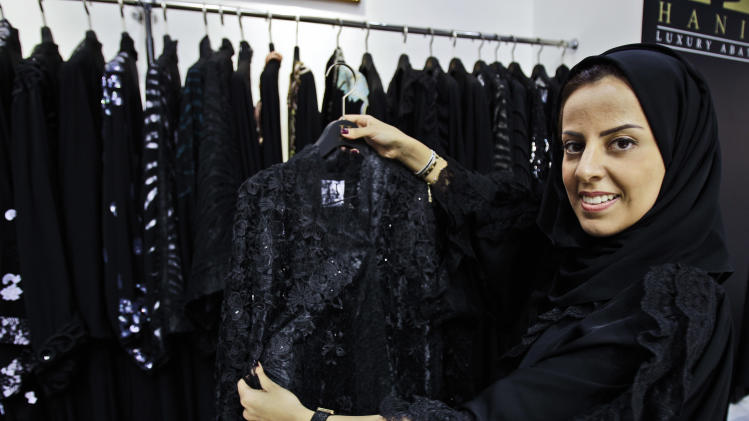 In this Saturday, April 13, 2013 photo, Saudi fashion designer Hania al-Braikan presents an abaya selling for about $1500 at a bridal exhibition in Dubai, United Arab Emirates.  Just a few years ago, Gulf Arab women usually only felt comfortable showing off their fashion sense at ladies-only parties or family gatherings. In public, at least in their home countries, the standard all-black abaya _ a simple floor-length covering and accompanying head scarf _ was the only culturally accepted option. But now a new generation of abaya designers are giving the traditional garment a twist with choices of fabric, designs and even some expensive bling to allow Gulf women a host of style options. (AP Photo/Kamran Jebreili)