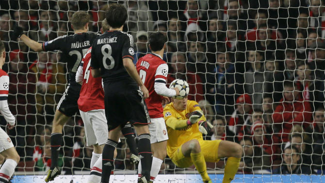 Bayern's Thomas Mueller, left, scores his side's 2nd goal past Arsenal goalkeeper Wojciech Szczesny, right, during a Champions League, round of 16, first leg soccer match between Arsenal and Bayern Munich at Arsenal's Emirates stadium in London, Tuesday, Feb.  19, 2013.(AP Photo/Alastair Grant)