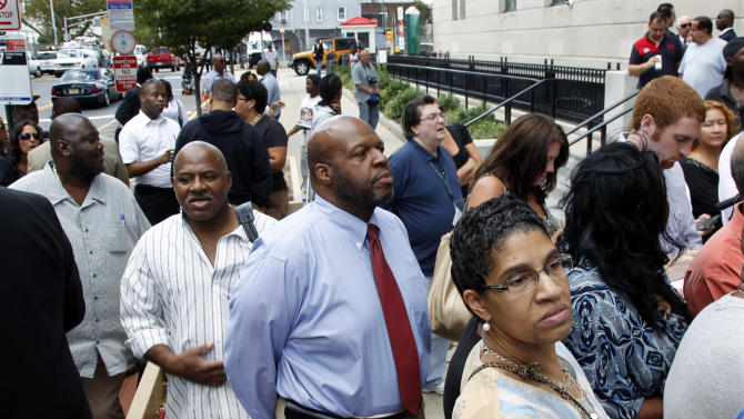 People stop to listen outside the Federal courthouse Monday, Sept. 10, 2012, in Trenton, N.J., as U.S. Attorney Paul Fishman announces that Federal agents arrested Trenton Mayor Tony Mack, the mayor of New Jersey's capital city, earlier Monday as part of an ongoing corruption investigation into bribery allegations related to a parking garage project that was concocted as part of an FBI sting operation. Mack, his brother, Ralphiel, and convicted sex offender Joseph Giorgianni, a Mack supporter who owns a Trenton sandwich shop, were accused of conspiring to obstruct, delay and affect interstate commerce by extortion under color of official right. (AP Photo/Mel Evans)