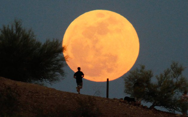 "A runner makes his way along a trail on a butte in front of the ""supermoon""  at Papago Park in Phoenix, Arizona May 5, 2012. A ""supermoon"" will light up Saturday's night sky, May 5, in a once-a-year cosmic show, overshadowing a meteor shower from remnants of Halley's Comet, the U.S. space agency NASA said. The Moon will seem especially big and bright since it will reach its closest spot to Earth at the same time it is in its  full phase, NASA said."