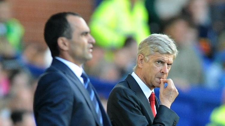 Arsenal manager Arsene Wenge, right, reacts during the English Premier League soccer match between Everton and Arsenal at Goodison Park, in Liverpool, England, Saturday, Aug. 23, 2014. (AP Photo/Rui Vieira)