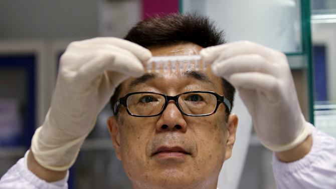Group Leader, Dr Masafumi Inoue of Agency for Science Technology and Research's (A*STAR) Experimental Therapeutics Centre holds up a sample to be tested with the Zika virus diagnostic test kit at their laboratory in Singapore