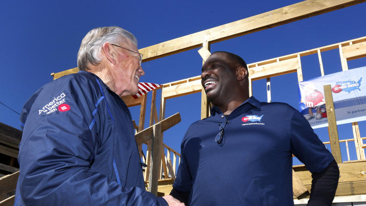 Former NFL head coach Joe Gibbs, left, and Former NFL quarterback and MVP of Super Bowl XXII Doug Williams talk to each other at the launch of M&M'S 'M' Prove America' campaign, which is designed to fund the construction of Habitat for Humanity homes across the country, on Friday, Feb. 1, 2013 in New Orleans. (Jonathan Bachman / AP Images for Habitat For Humanity)