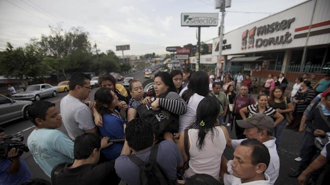People ride in the back of a pick up truck during the second day of a suspension of public transport services in Mejicanos, El Salvador