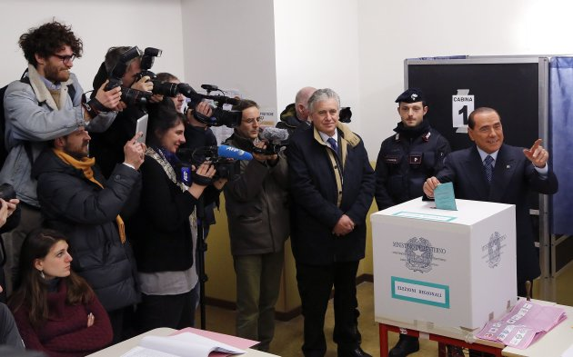 Former PM Berlusconi gestures as he casts his vote at the polling station in Milan