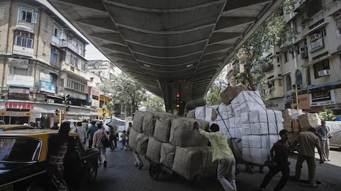 Workers move handcarts loaded with goods under a flyover at a market in Mumbai