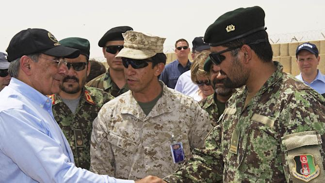 US Secretary of Defense Leon Panetta, left.  greets an Afghan military leader as he makes an unannounced visit to Camp Dwyer,  Sunday July 10, 2011, in  southern Afghanistan.  Panetta visited troops in southern Afghanistan  as part of his first trip to the country since taking up his post and ahead of a withdrawal of some US forces. (AP Photo/Paul J. Richards, Pool)