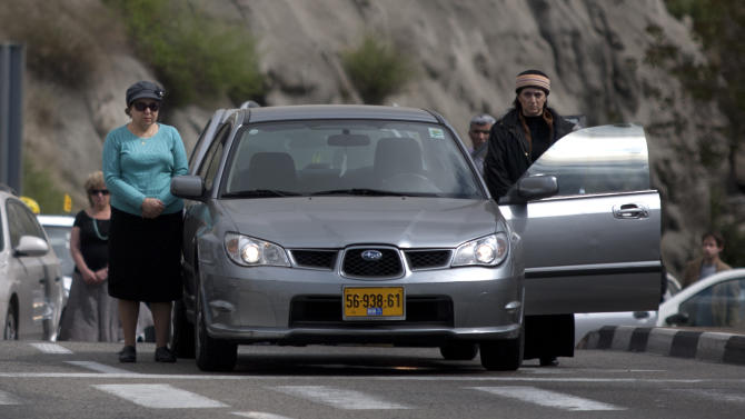 Israelis stand still next to their cars on a highway as a two-minute siren sounds in memory of victims of the Holocaust in Jerusalem, Thursday, April 19, 2012. The day is one of the most solemn on Israel's calendar. Restaurants and places of entertainment shut down, and radio and TV programming focuses on Holocaust documentaries and interviews with survivors. (AP Photo/Sebastian Scheiner)