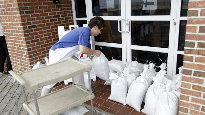 A restaurant worker piles sand bags at the entrance of the business as Hurricane Sandy approaches the Atlantic Coast, in Ocean City, Md., on Saturday, Oct. 27, 2012. ( AP Photo/Jose Luis Magana)