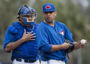 Toronto Blue Jays starting pitcher Ricky Romero, right, talks with Blue Jays catcher Henry Blanco, left, moments before being pulled against the Minnesota Twins during second inning MLB Grapefruit League baseball action Dunedin, Fla., on Tuesday, Feb. 26, 2013. THE CANADIAN PRESS/Nathan Denette