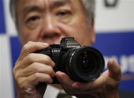 Olympus Corp's President Hiroyuki Sasa poses with his company's new OM-D E-M1 digital camera during its unveiling in Tokyo in this September 10, 2013 file photo. REUTERS/Toru Hanai/Files
