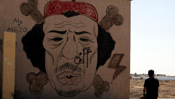 A  Libyan man sits near  a mocking graffiti of al-Gaddhafi, in Benghazi, Libya, Monday, Sept. 20, 2012.  In front of Benghazi's stock market, there are lakes of sewage in the street, and the grandest hotel here is a gloomy hulk with broken windows and dim corridors. The city that was the site of a deadly attack on the U.S. Consulate was the heart of Libya's revolution, and now its residents are discontent with the new leadership in Tripoli.  (AP photo/Mohammad Hannon)