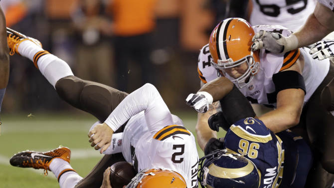 Cleveland Browns quarterback Johnny Manziel (2) is sacked by St. Louis Rams defensive end Michael Sam (96) in the fourth quarter of a preseason NFL football game Saturday, Aug. 23, 2014, in Cleveland. (AP Photo/Tony Dejak)