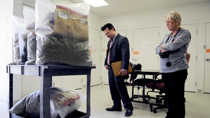 This March 14, 2013 photo shows Rocky Mountain Miracles dispensary owner Alvilda Hillery and her attorney Sean McAllister viewing the 36 pounds of medical marijuana that were seized from her shop, along with 600 plants, during a raid. Colorado Springs medical dispensary owner Alvida Hillery sued police to return her 604 pot plants or pay $3.3 million in compensation after she was acquitted of drug-cultivation charges but later dropped the suit in exchange for the city granting her a new dispensary license.(AP Photo/The Gazette, Michael Ciaglo)