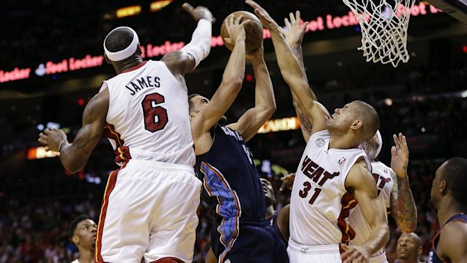 Miami Heat's LeBron James (6) and Shane Battier (31) block Charlotte Bobcats' Jeffrey Taylor (44) during the second half of a NBA basketball game in Miami, Sunday, March 24, 2013. The Heat won 109-77. (AP Photo/J Pat Carter)