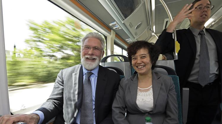 Mayor R. Rex Parris of Lancaster, Calif., and Stella Li, president of BYD Motors, take a demonstration ride on an electric bus at the announcement of the opening of an electric bus manufacturing plant by the Chinese firm BYD, in the Southern California city of Lancaster Wednesday, May 1, 2013. BYD, known as Build Your Dream, is a major producer of batteries and electric vehicles in China. (AP Photo/Reed Saxon)