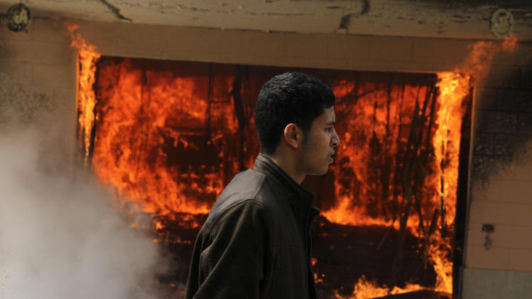 An Egyptian man walks on the grounds of a police officer's club as a fire set by protesters burns in Cairo, Egypt, Saturday, March 9, 2013. An Egyptian court on Saturday confirmed the death sentences against 21 people for taking part in a deadly soccer riot but acquitted seven police officials for their alleged role in the violence, touching off furious protests in Cairo that torched the soccer federation headquarters and a nearby police club.(AP Photo/Ahmed Gomaa)