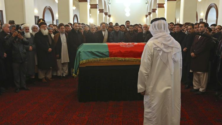 A foreign diplomat pays respects to the flag-covered coffin of Afghan Vice-President Marshal Fahim during his burial ceremony at the Presidential Palace in Kabul
