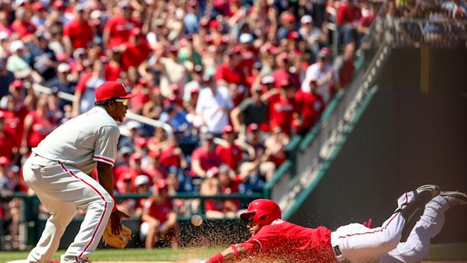 Philadelphia Phillies third baseman Maikel Franco fields a ball as Washington Nationals' Yunel Escobar (5) slides into third base for a triple in the fifth inning during a baseball game, Sunday, May 24, 2015, at Nationals Park in Washington. (AP Photo/Andrew Harnik)
