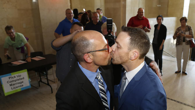 Rich Gillard, left, and Andrew Petroll kiss after their marriage ceremony at the Milwaukee County Courthouse on Friday, June 6, 2014, in Milwaukee. Earlier Friday, a federal judge struck down the state's ban on gay marriage. (AP Photo/Jeffrey Phelps)