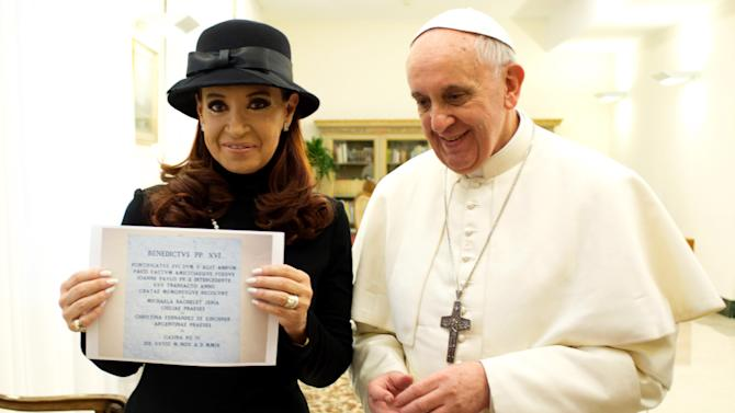 """In this photo provided by the Vatican newspaper L'Osservatore Romano, Pope Francis stands by Argentine President Cristina Fernandez showing a picture of a marble plaque commemorating the 1984 peace and friendship treaty between Argentina and Chile as they meet at the Pope's temporary apartments in the Santa Marta hotel at the Vatican, Monday, March 18, 2013. Inscription in Latin reads: """"In the fifth year of Benedict XVI's pontificate, after 25 years from the peace and friendship treaty reached with the mediation of Pope John Paul II, Chilean President Michelle Bachelet Jeria and Argentine President Christina Fernandez de Kirchner in remembrance of the efforts, Casina Pio IV, on November 28, 2009."""" (AP Photo/L'Osservatore Romano)"""