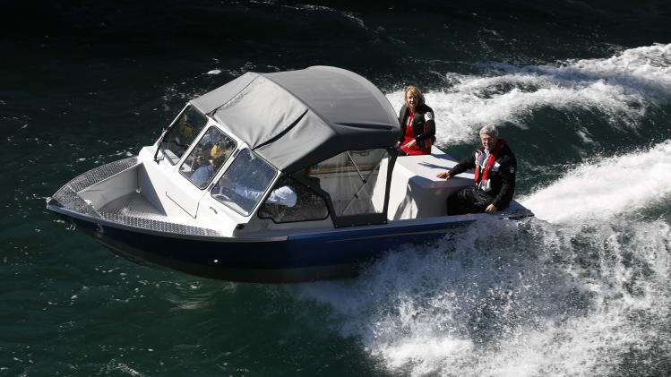 Canada's PM Harper and his wife Laureen ride a boat on the Yukon River at Miles Canyon near Whitehorse, Yukon