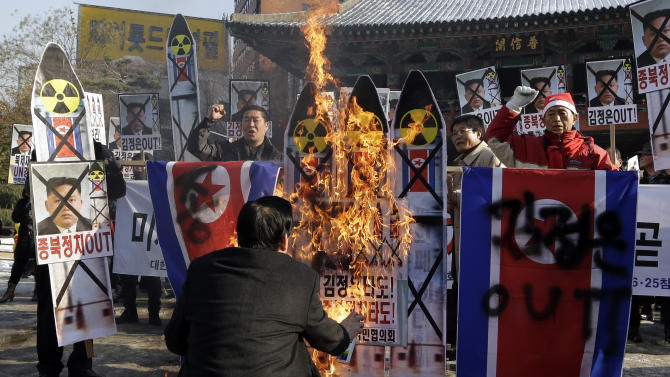 South Korean protesters burn the pictures of North Korean leader Kim Jong Un, North Korean flags and mock missiles during a rally denouncing North Korea's rocket launch in Seoul, South Korea, Wednesday, Dec. 12, 2012. North Korea successfully fired a long-range rocket on Wednesday, defying international warnings as the regime of Kim Jong Un took a giant step forward in its quest to develop the technology to deliver a nuclear warhead. (AP Photo/Lee Jin-man)