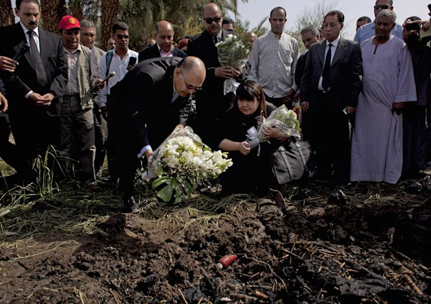 Japanese travel agent Okumura Hatsuko, bottom right, and Luxor's Govornor Ezzat Saad, bottom left, lay flowers to pay respect to Japanese tourists that died from a hot air balloon accident, in Luxor,