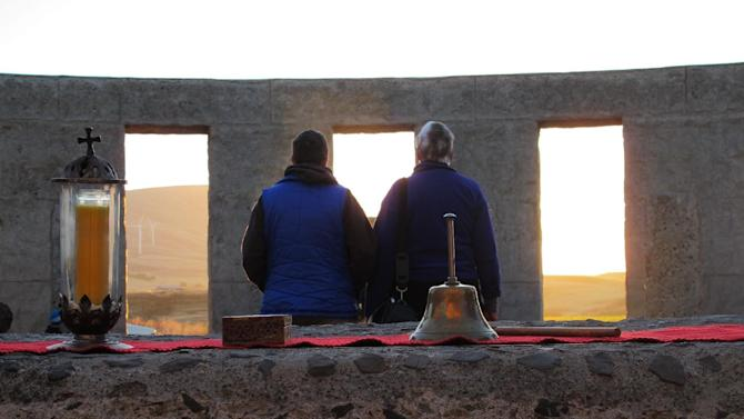 Vicky Lightning, right, walks with a friend during the summer solstice at a Stonehenge replica in Maryhill, Wash., on Saturday, June 21, 2014. The replica serves as a monument to the World War I dead from Klickitat County, Wash. Lightning says she she often worships at the Stonehenge replica. (AP Photo/Nigel Duara)