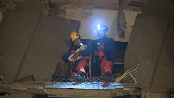 Rescuers stand on a ledge of a collapsed building as one of them carries a 10-day-old baby after an earthquake hit the southern city of Tainan