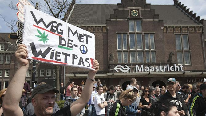 """A demonstrator holds a sign reading """"get rid of the weed pass"""" during a demonstration which started at the Maastricht train station, southern Netherlands, Tuesday May 1, 2012. A policy barring foreign tourists from buying marijuana in the Netherlands goes into effect in parts of the country Tuesday, with a protest planned in the southern city of Maastricht. Weed is technically illegal in the Netherlands, but it is sold openly in small amounts in designated cafes under the country's famed tolerance policy. The government has said that as of May 1, only holders of a """"weed pass"""" will be allowed to purchase the drug, and nonresidents aren't eligible. (AP Photo/Peter Dejong)"""
