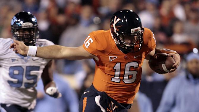 Virginia quarterback Michael Rocco (16) hurdles North Carolina cornerback Terry Shankle (24) during the first half of an NCAA college football game at Scott stadium  Thursday, Nov. 15, 2012 in Charlottesville, VA (AP Photo/Steve Helber)