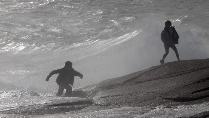 A man and his daughter scramble across the shoreline rocks after being hit by a wave on Sunday, Aug. 28, 2011 in Peggy's Cove, Nova Scotia. Atlantic Canada is experiencing increased wind and rain as the effects of Irene, downgraded from a hurricane to a tropical storm, continues to move towards southern Quebec and Eastern Canada. (AP Photo/The Canadian Press, Mike Dembeck)