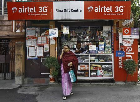 A woman speaks on her mobile phone after recharging it at a local stationary cum prepaid mobile recharge shop in Kolkata