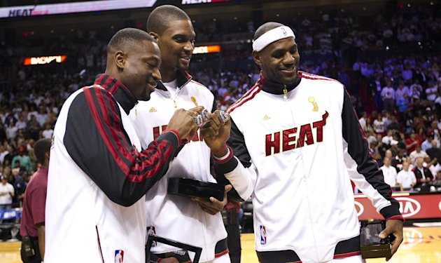 From left, Miami Heat's Dwyane Wade, Chris Bosh and LeBron James pose with their 2012 NBA Finals championship rings during a ceremony before a basketball game against the Boston Celtics, Tuesday, Oct. 30, 2012, in Miami. (AP Photo/J Pat Carter)