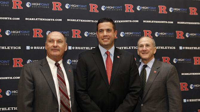 FILE - In this Nov. 20, 2012 file photo, Rutgers athletic director Tim Pernetti, center, poses with Rutgers President Robert Barchi, right, and Big Ten Conference Commissioner Jim Delany during a news conference in Piscataway, N.J., after they announced that Rutgers will join the Big Ten. A person familiar with the decision says Pernetti is out as Rutgers athletic director. The person spoke on condition of anonymity because an official announcement has not been made yet. The school will hold a press conference on campus at 1 p.m. Friday, April 5, 2013. Pernetti dismissed basketball coach Mike Rice Wednesday after a videotape aired showing him shoving, grabbing and throwing balls at players in practice and using gay slurs. The scandal has now cost Pernetti his job some five months after he didn't fire Rice when the video first became available. (AP Photo/Mel Evans, File)