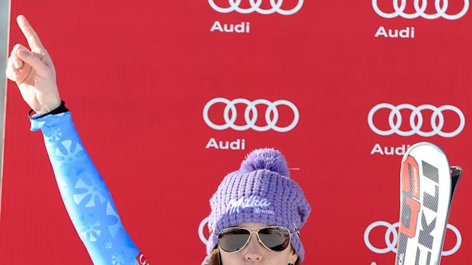 Tina Maze, of Slovenia, celebrates on the podium after placing second in an Alpine Ski World Cup women's downhill, in Cortina D'Ampezzo, Italy, Saturday, Jan.19, 2013. (AP Photo/Giovanni Auletta)