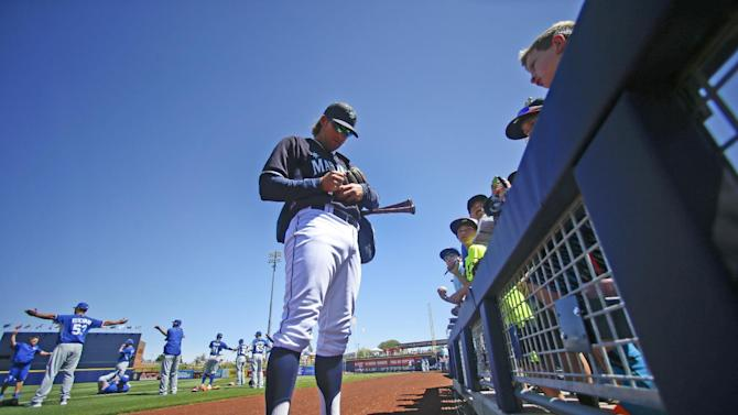 Seattle Mariners shortstop Brad Miller signs autographs prior to the start of a spring training baseball game against the Kansas City Royals Thursday, March 26, 2015, in Peoria, Ariz.  (AP Photo/Lenny Ignelzi)