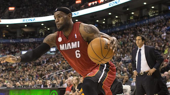 Miami Heat's LeBron James drives at the Toronto Raptors' defence as Heat's Head Coach Erik Spoelstra looks on during first half NBA basketball action in Toronto on Sunday, March 17, 2013.  (AP Photo/The Canadian Press, Chris Young)