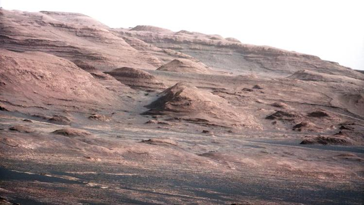 FILE - This file image provided by NASA shows the base of Mount Sharp on Mars. The Curiosity rover is set to drive toward the mountain in mid-February after drilling into a rock. The image was taken by Curiosity's 100-millimeter Mast Camera on Aug. 23, 2012. Scientists enhanced the color in one version to show the Martian scene under the lighting conditions we have on Earth, which helps in analyzing the terrain. (AP Photo/NASA/JPL-Caltech/MSSS, File)