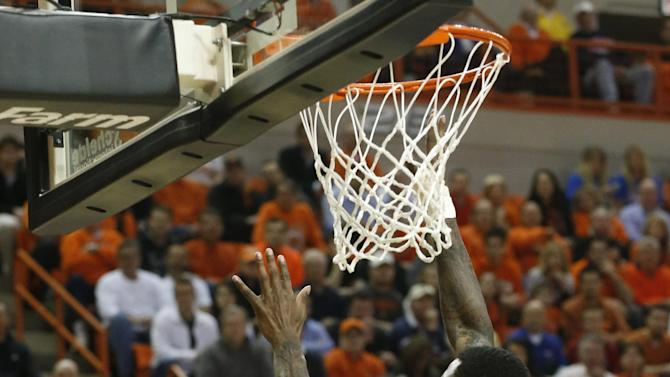 Oklahoma State guard Brian Williams (4) shoots as Kansas forward Jamari Traylor (31) defends during the first half of an NCAA college basketball game in Stillwater, Okla., Wednesday, Feb. 20, 2013. (AP Photo/Sue Ogrocki)