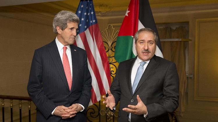 US Secretary of State John Kerry, left, looks on as Jordanian Foreign Minister Nasser Judeh makes a statement about the ongoing humanitarian crisis and violence in Syria on Wednesday, Feb. 19, 2014, in Paris. (AP Photo/ Evan Vucci)